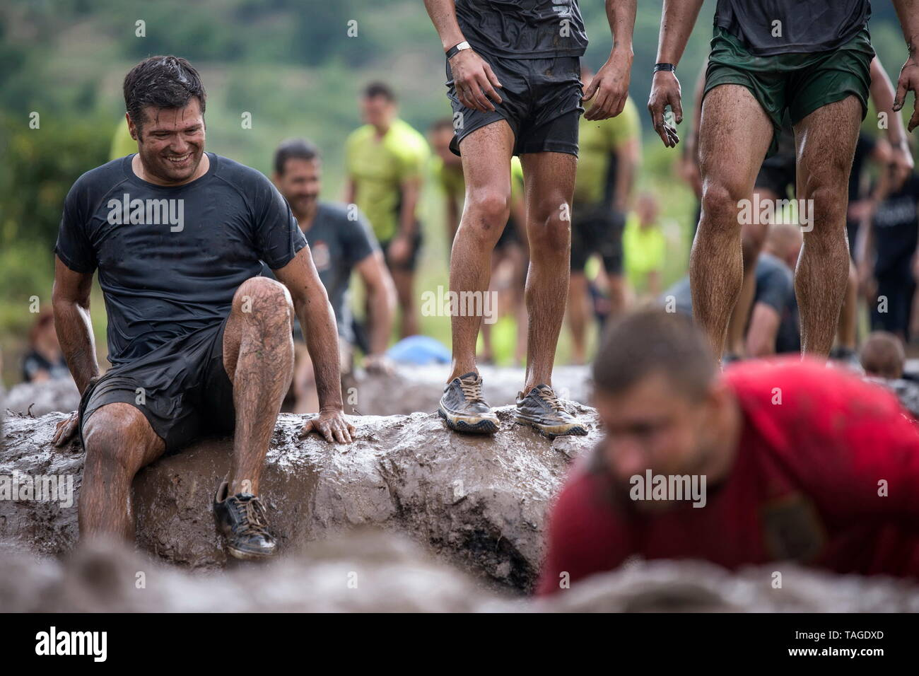SOFIA, BULGARIA - JULY 7th 2018 - a smiling man is having fun covered with mud and trying to overcome the obstacle course in a strength race - Stock Image