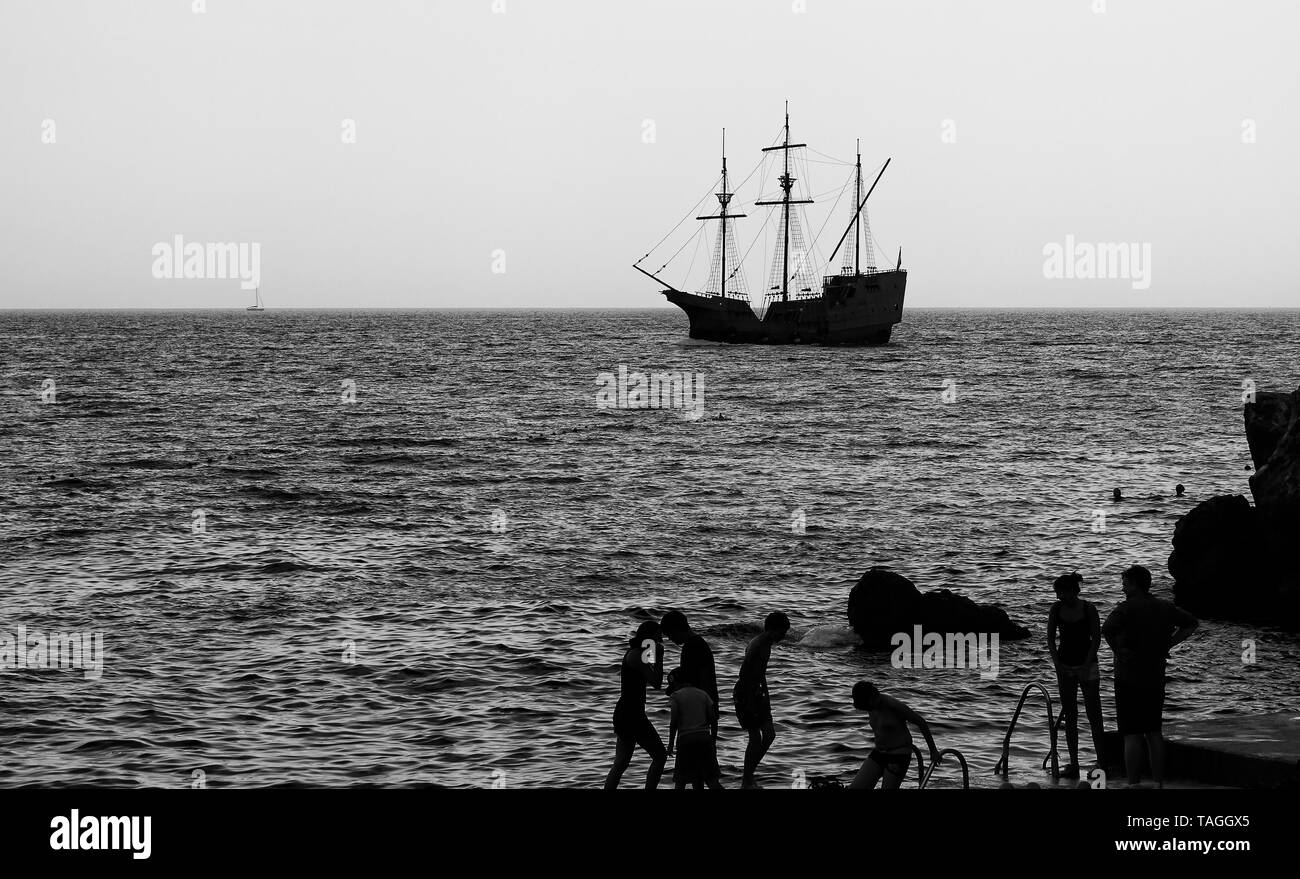 Silhouettes of people on the beach and the old sailing ship in the distance, processed in black and white - Stock Image