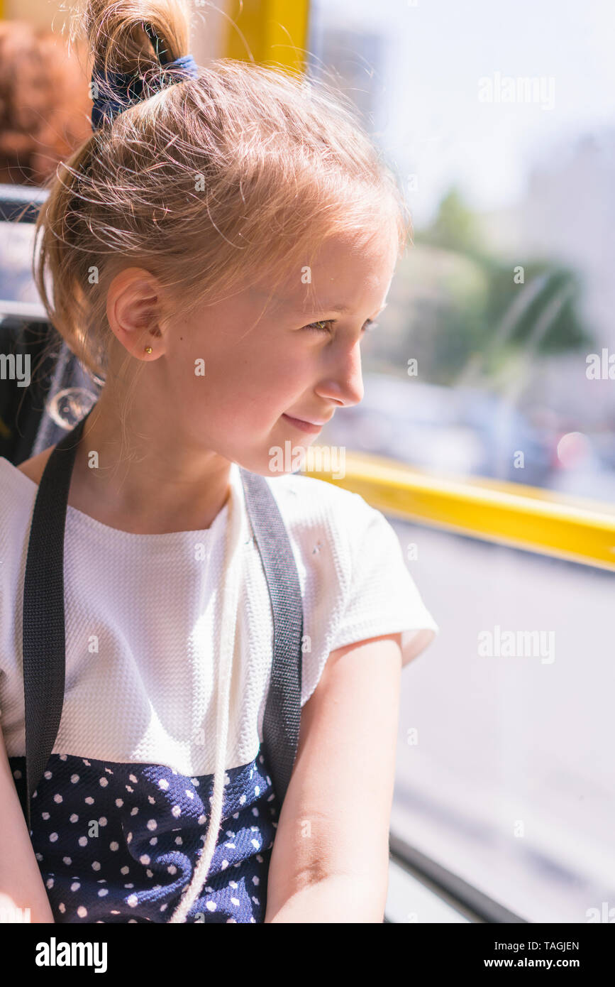 A little girl is going by bus. Schoolgirl sitting in school bus and ready for her first ride. vertical photo. Stock Photo
