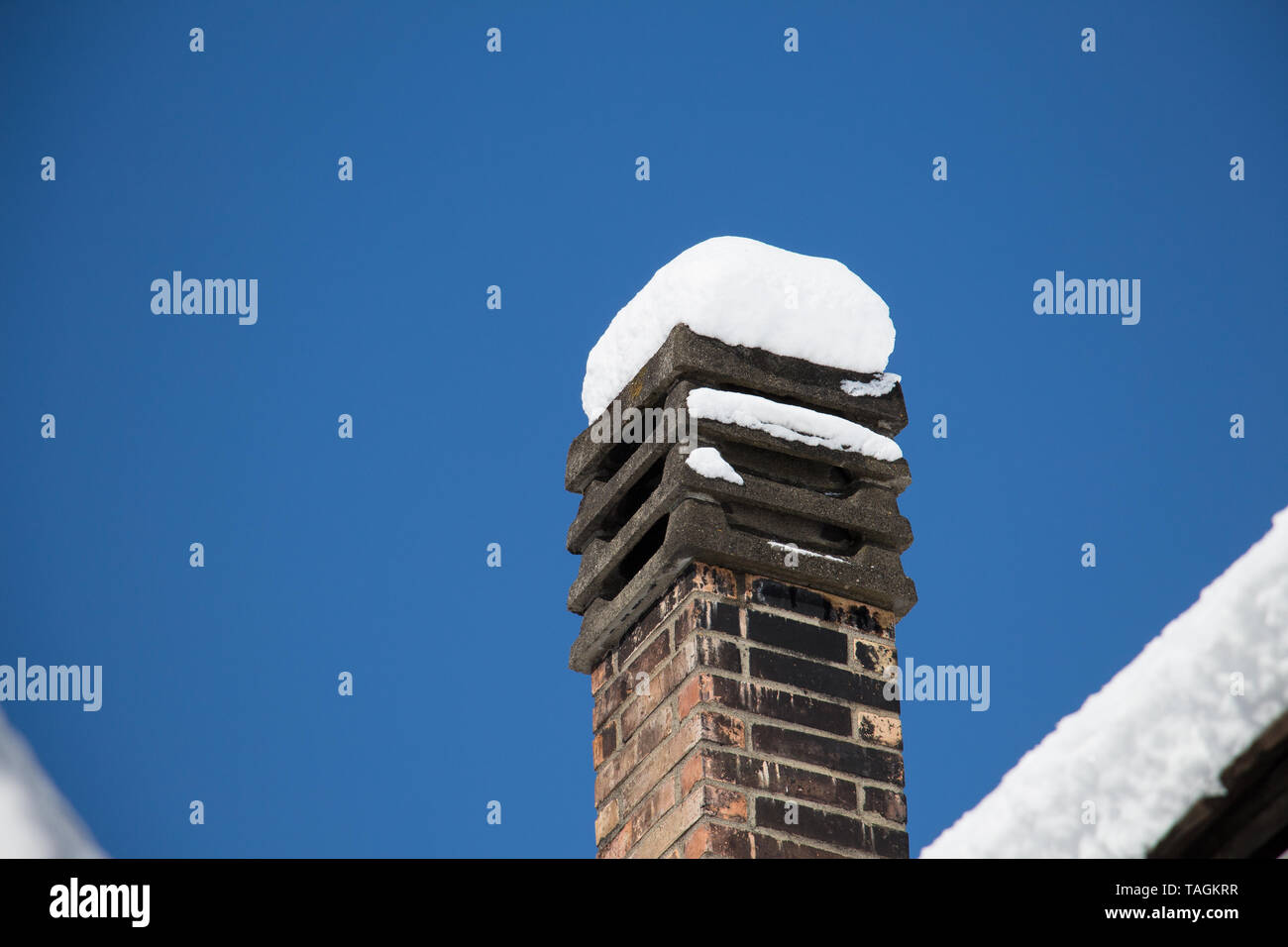 snow hood on a soot covered chimney - Stock Image