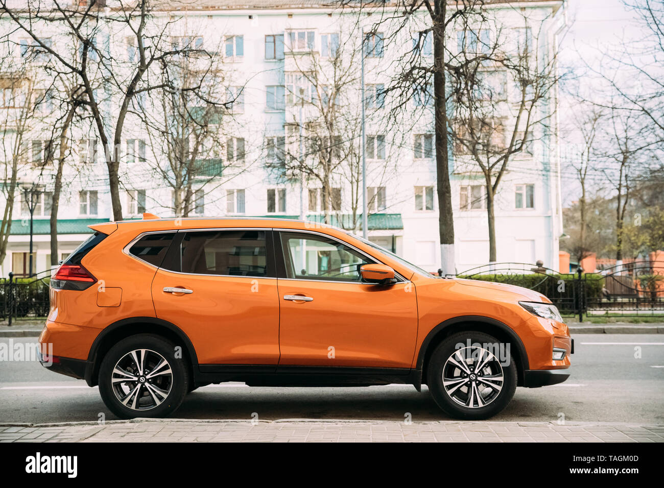Gomel, Belarus - April 16, 2019: Orange Nissan X-Trail third generation Car Parked At Street. Side View - Stock Image