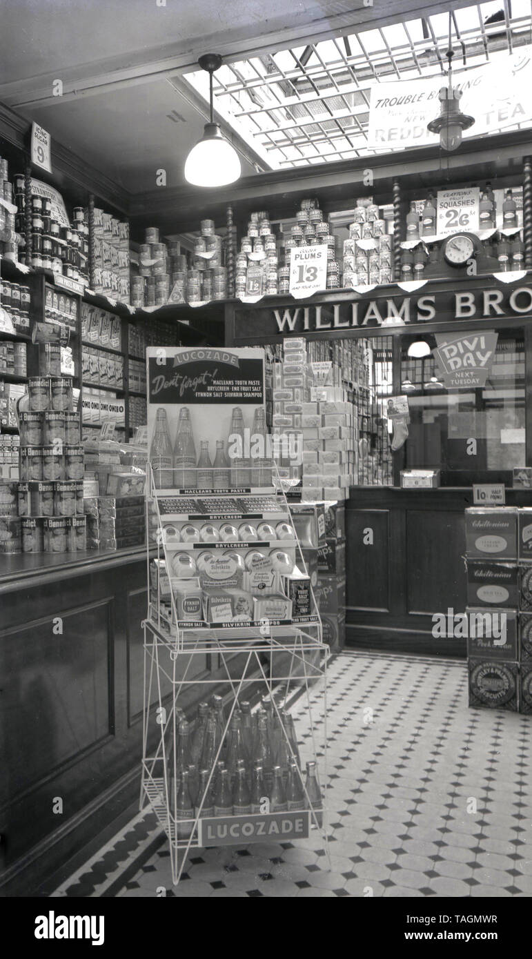 1940s, historical, inside view of a Williams Brothers grocery and provisions store, England, UK, showing products of the era, including canned fruits, squashes, icing sugar, Strawberry Jam stacked high in the shop and a sign for 'Divi Day' next Tuesday. Also a display stand for Lucozade, the fizzy drink that was promoted to aid recovery from illness. Traditional family grocery and provision stores like this were a common feaure of the British high sreet in this era, only declining in the late 1960s due to competition from the emerging supermarkets. - Stock Image