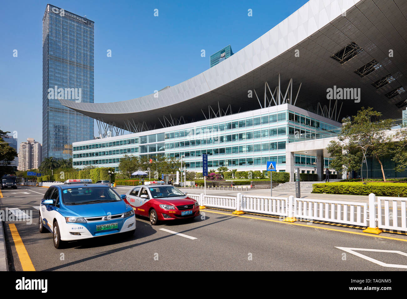 Blue electric and red petrol taxi cabs passing by Shenzhen Civic Center. Shenzhen, Guangdong Province, China. - Stock Image