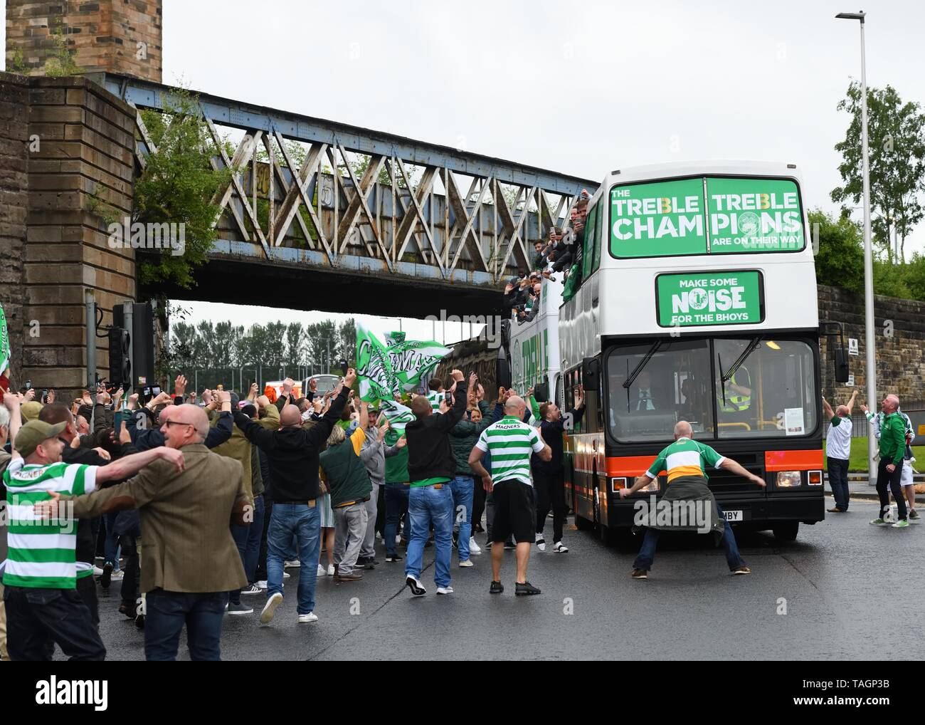 25th May, 2019. Glasgow, Scotland, UK, Europe. Scottish Cup winners, Celtic Football Club fans celebrate their teams achievement of three consecutive seasons winning all domestic trophies. The first time a domestic club has completed the triple treble in world football. Pictured are the players and staff aboard open top buses surrounded by exuberant fans Stock Photo