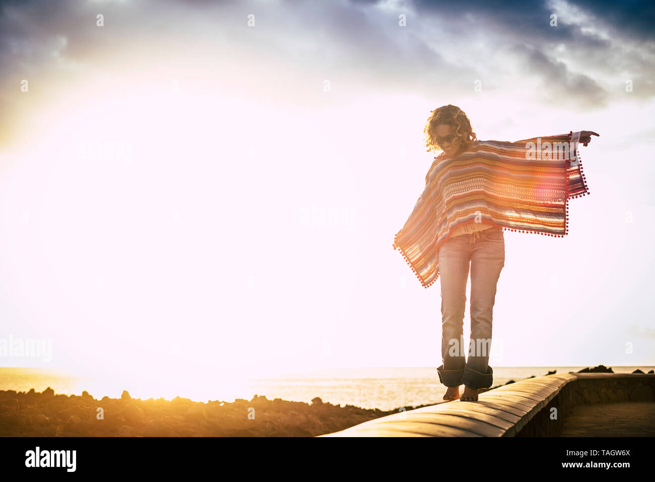 Young people enjoying outdoor leisure activity - beautiful cheerful woman walking barefoot in balance with coloured poncho - sunset and ocean in backg - Stock Image