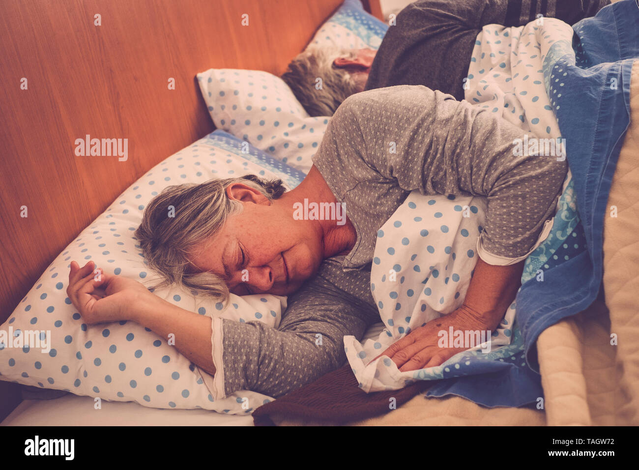 Caucasian people at home - old senior couple sleeping in the bedroom at the morning - retired lifestyle and real life moment - forever together concep Stock Photo