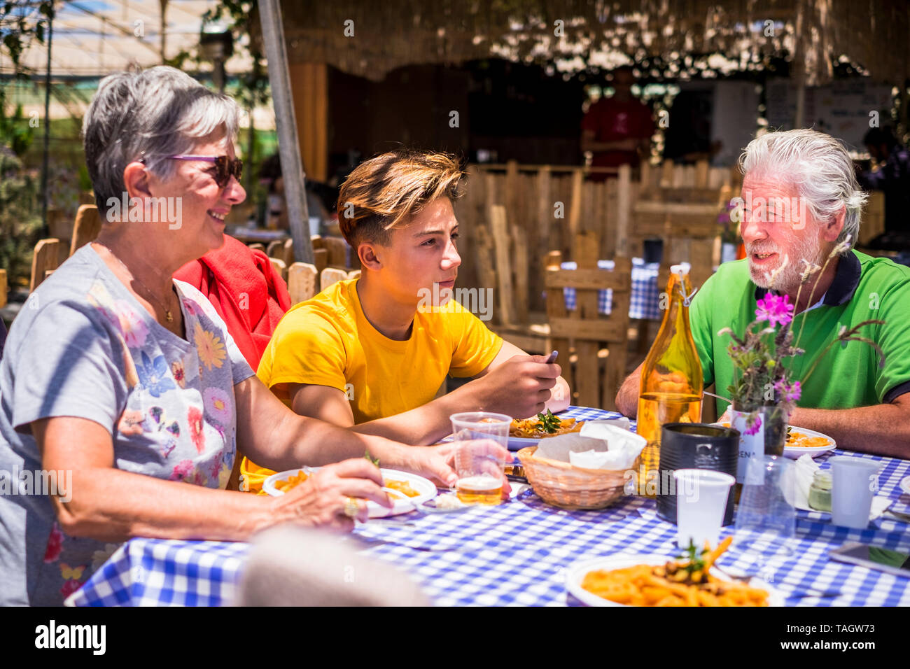 Active senior aged old people with grandson having lunh together outdoor in alternative restaurant - family concept with teenager and grandfathers tog Stock Photo