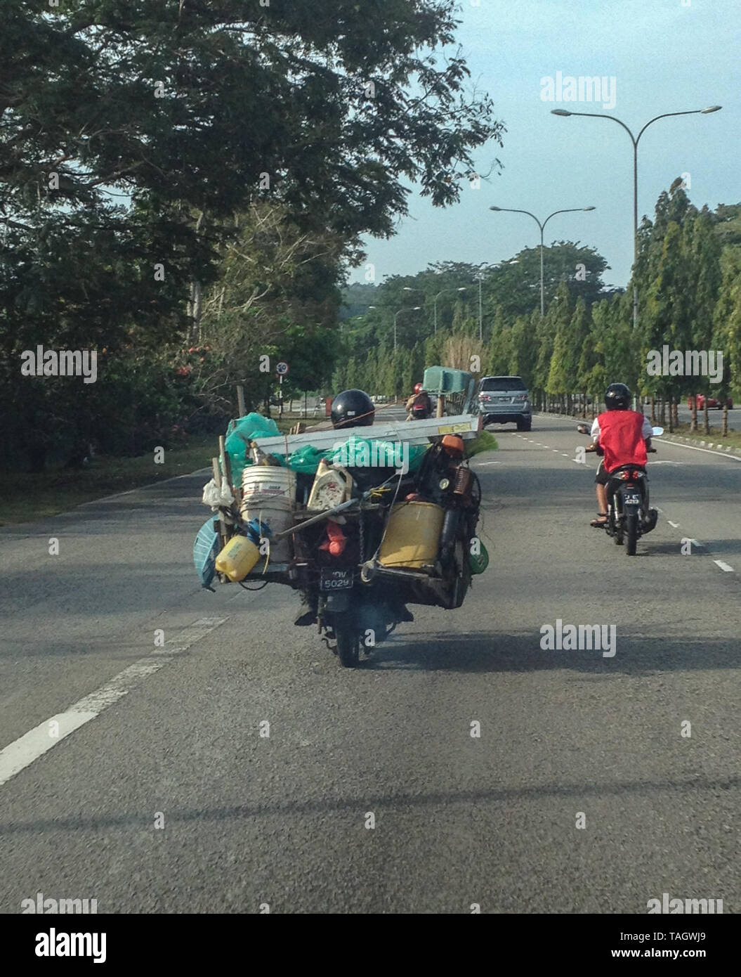 A motorcycle carrying excess baggage in Malaysia - Stock Image