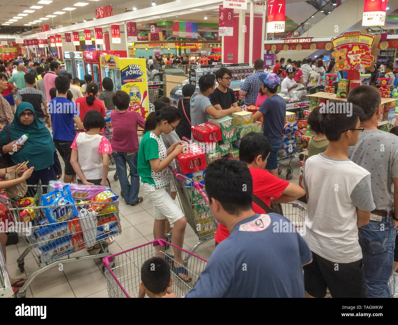 Shoppers queueing at supermarket checkouts for Chinese New Year celebrations - Stock Image