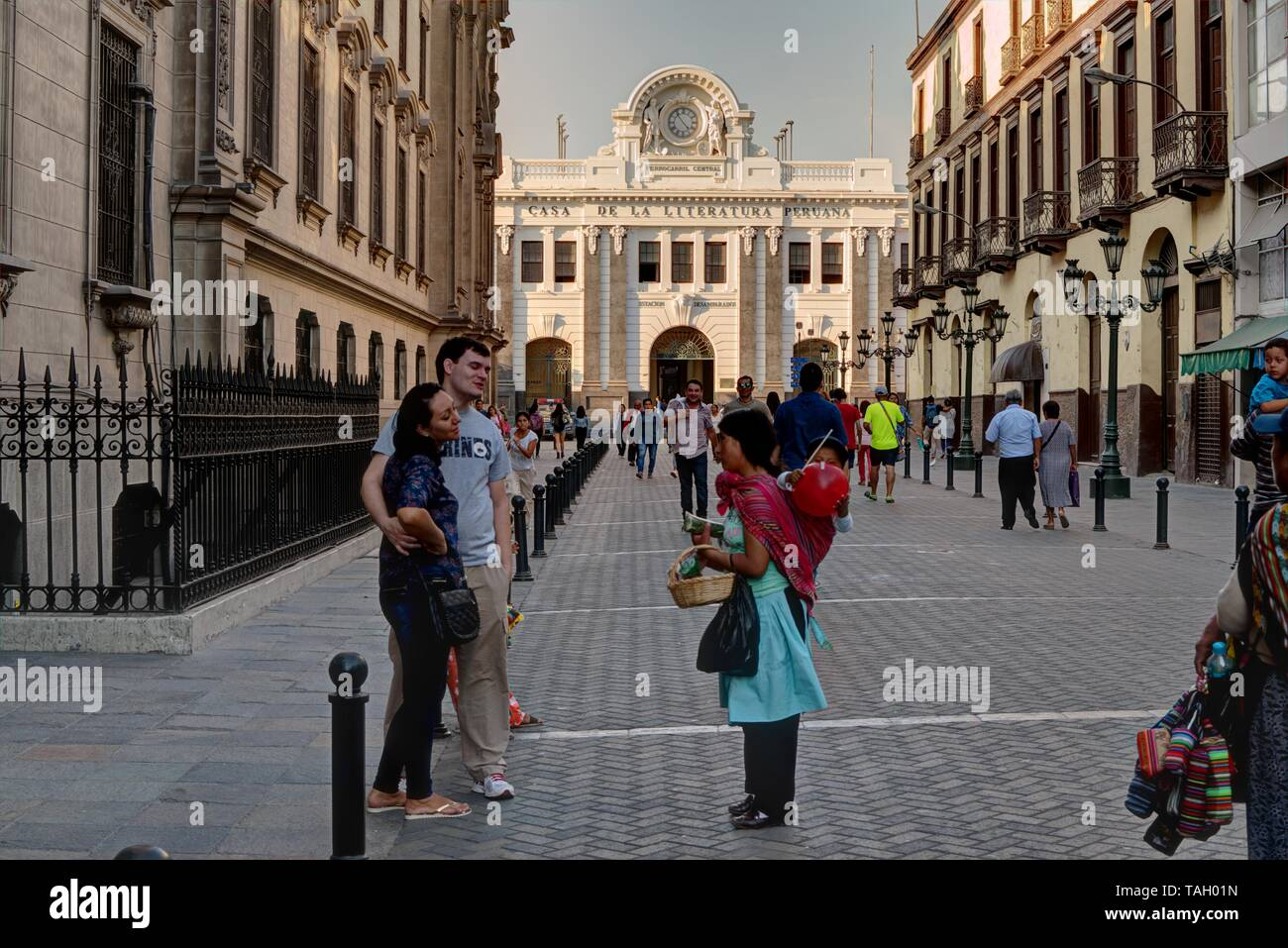 Lima, Peru - April 21, 2018: Woman with baby selling goods to tourists outside Casa de la Literatura Peruana which translates to House of Peruvian Lit - Stock Image