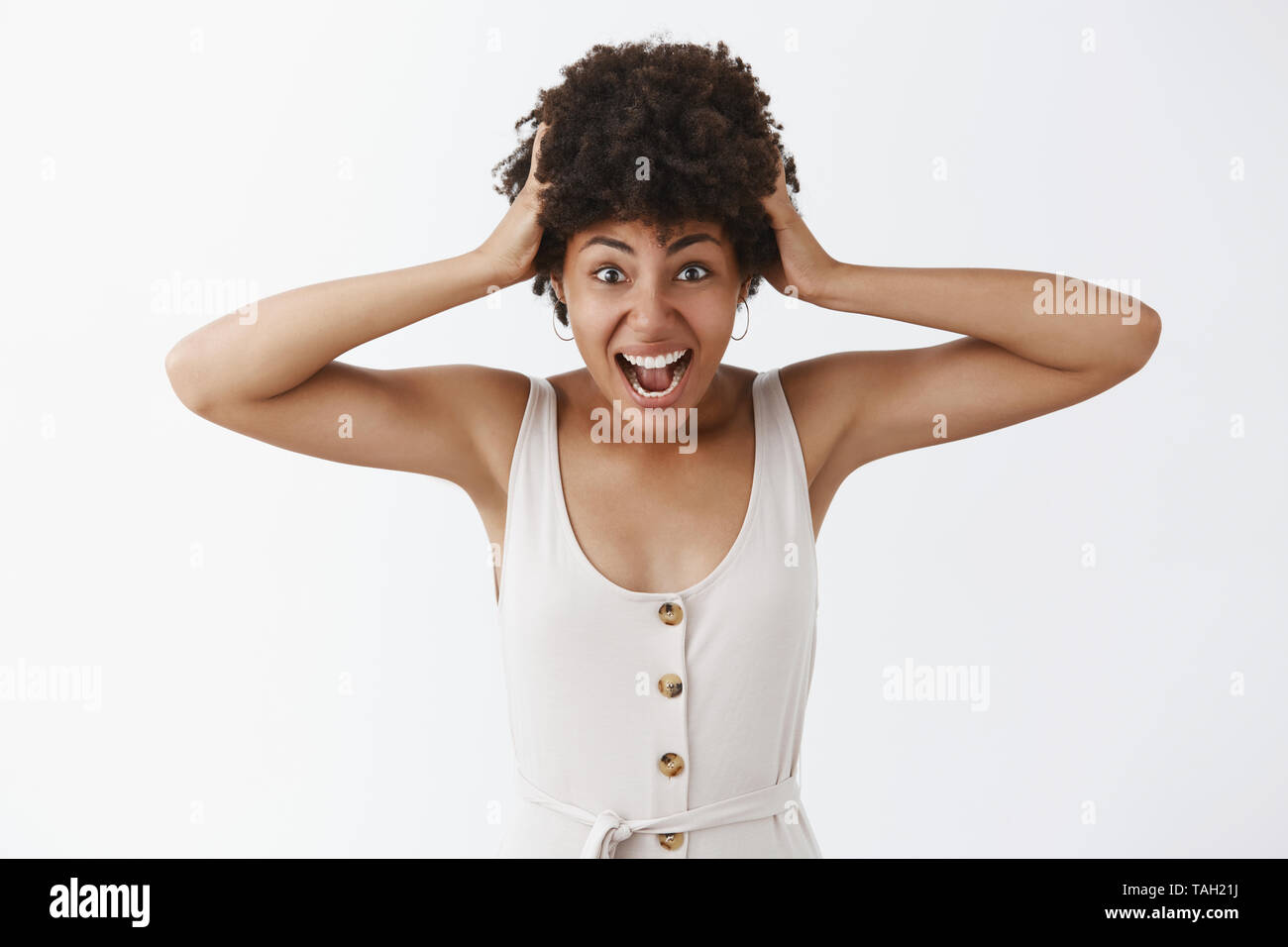 Studio shot of emotive distressed charming African American in white overalls pulling hair out of head yelling at camera grimacing and making worried - Stock Image