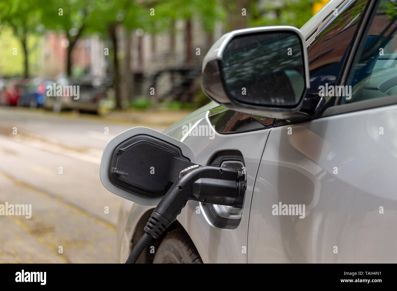 Electric car plugged into an EV charging station. - Stock Image