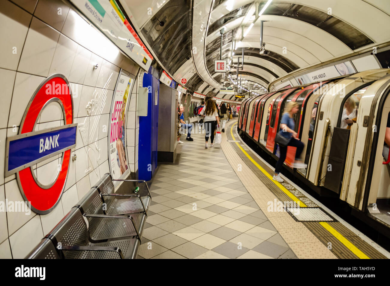 Passengers board a Central Line London underground Train at Bank subway station. - Stock Image