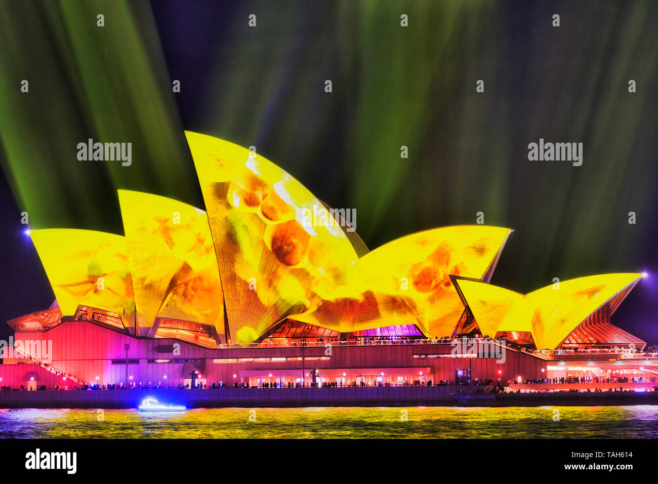 Sydney, Australia - 25 May 2018: Yellow fading light painted image of tiled sails of the SYdney Opera house under yellow streams of light in dark sky  - Stock Image