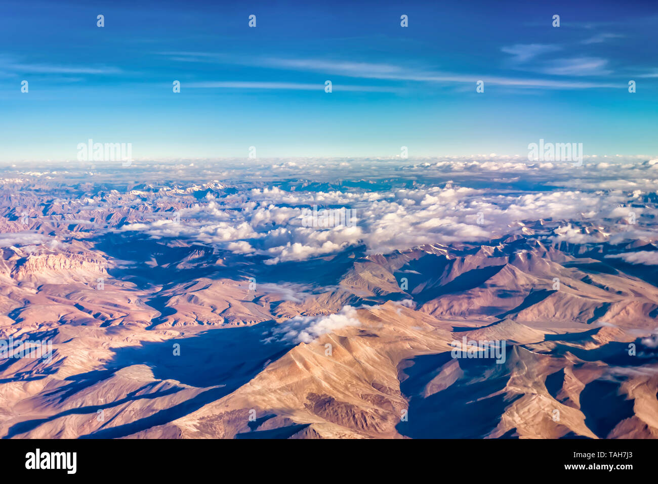 An aerial view of the barren mountains of the Zanskar range of inner Himalayas, India. Taken from a plane on an early July morning. - Stock Image