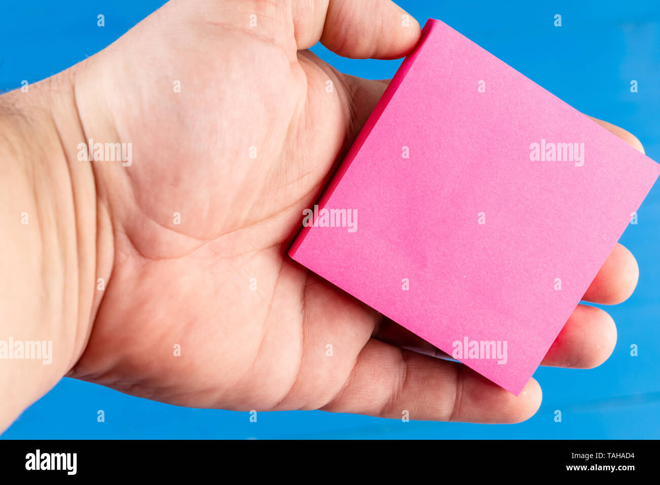 Front view colored background man hand palm holding sticky note. Things do - Stock Image
