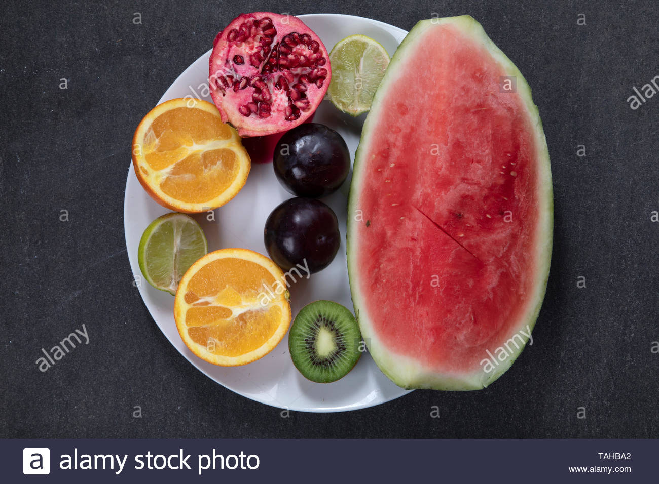 Fruit plate with watermelon, plums, kiwifruit, pomegrante, lime and oranges - Stock Image