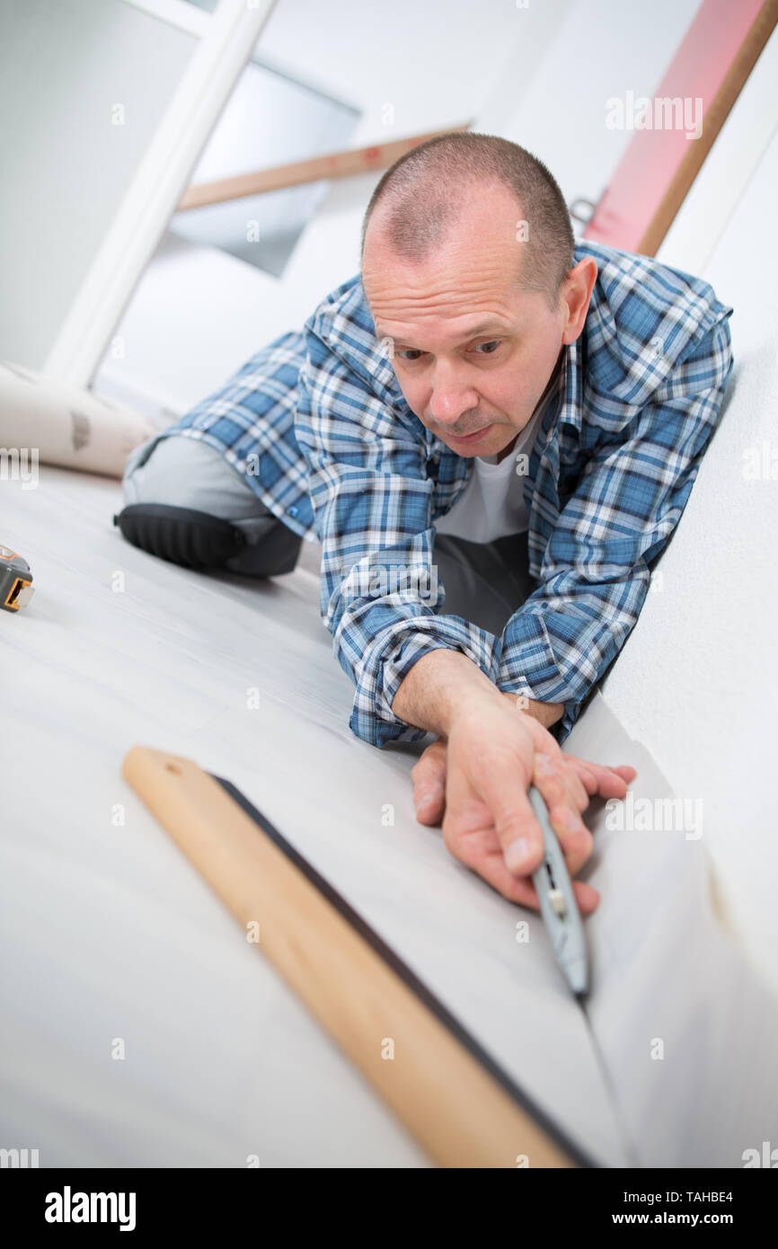 handyman fitting carpet while installation with cutter - Stock Image