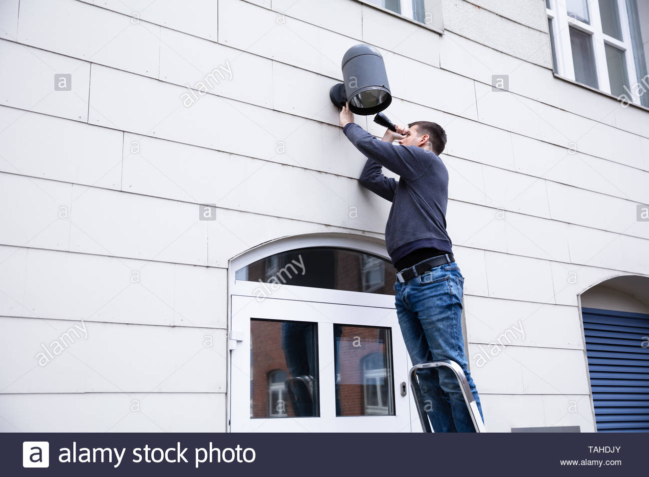 Young Serviceman Standing On Ladder Checking Outdoor Electric Lamp On Wall With Torch Light - Stock Image