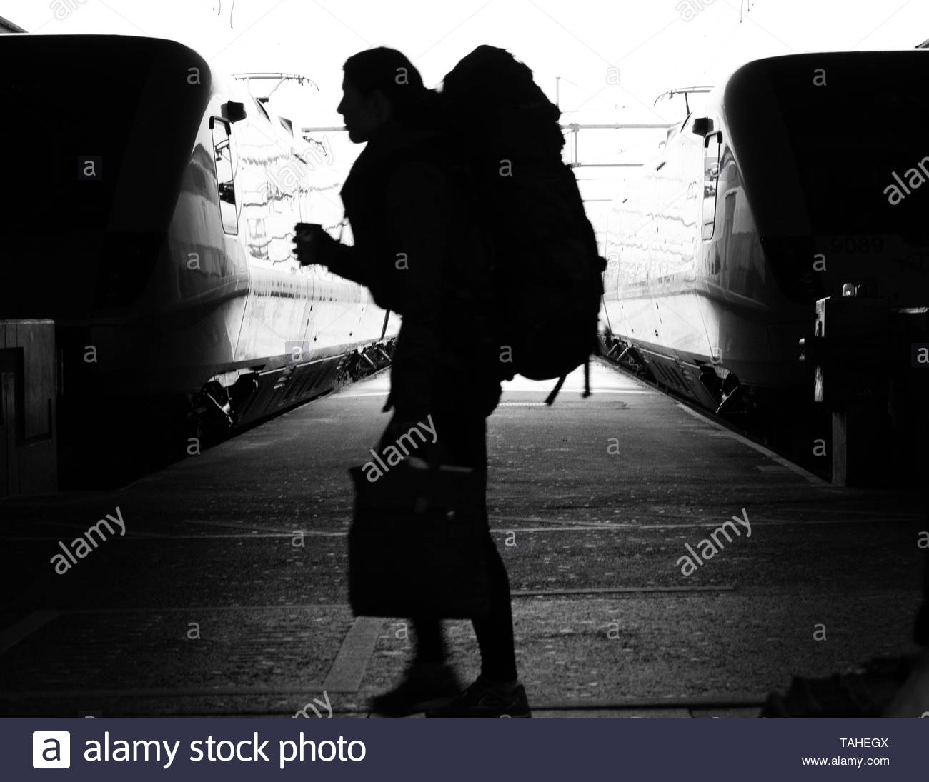 Traveler rushing with coffee in hand - Stock Image