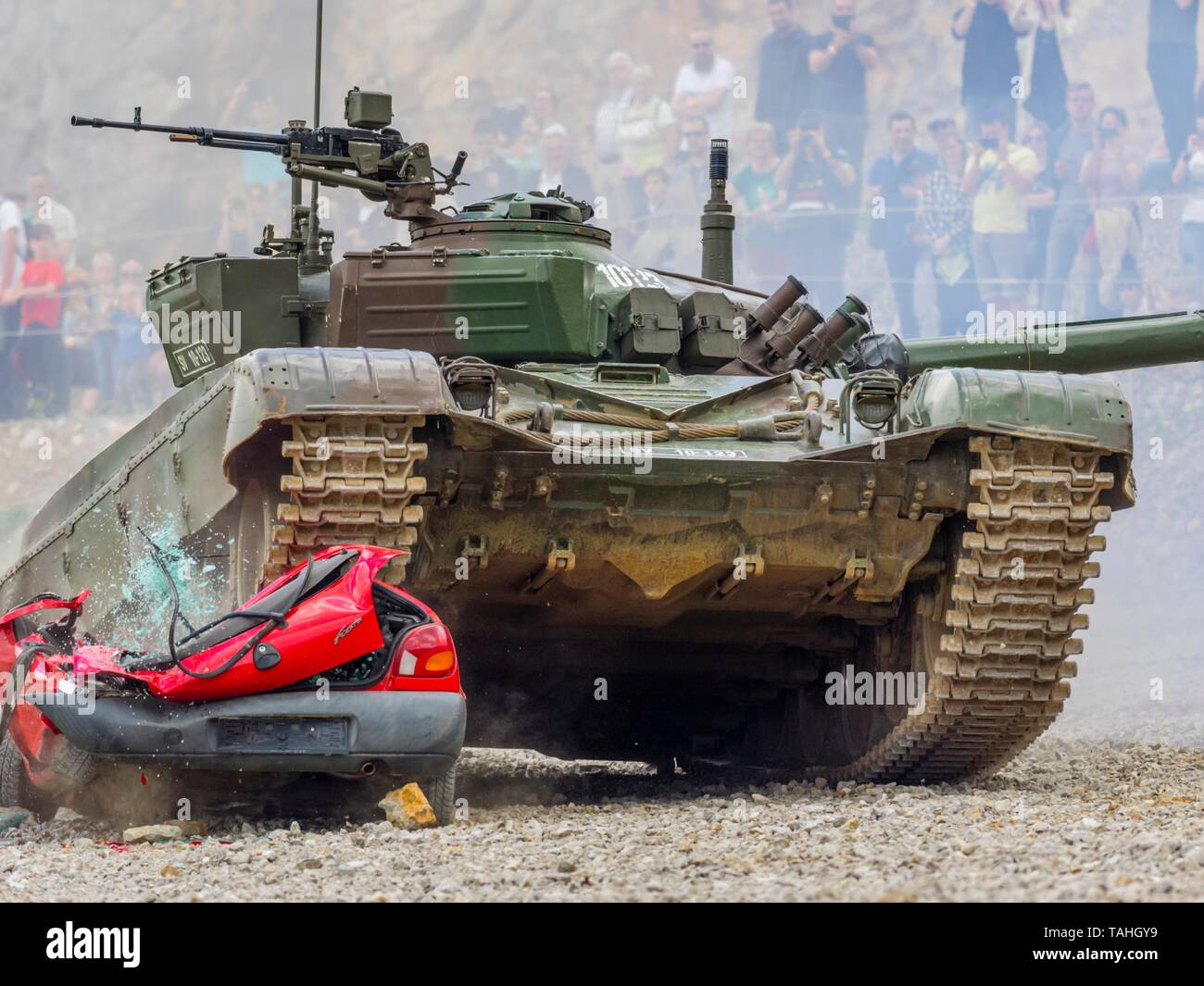 Tank drivin over hopeless car vehicle during public military demonstration in Pivka Slovenia M84 MBT driving towards camera front frontal view - Stock Image