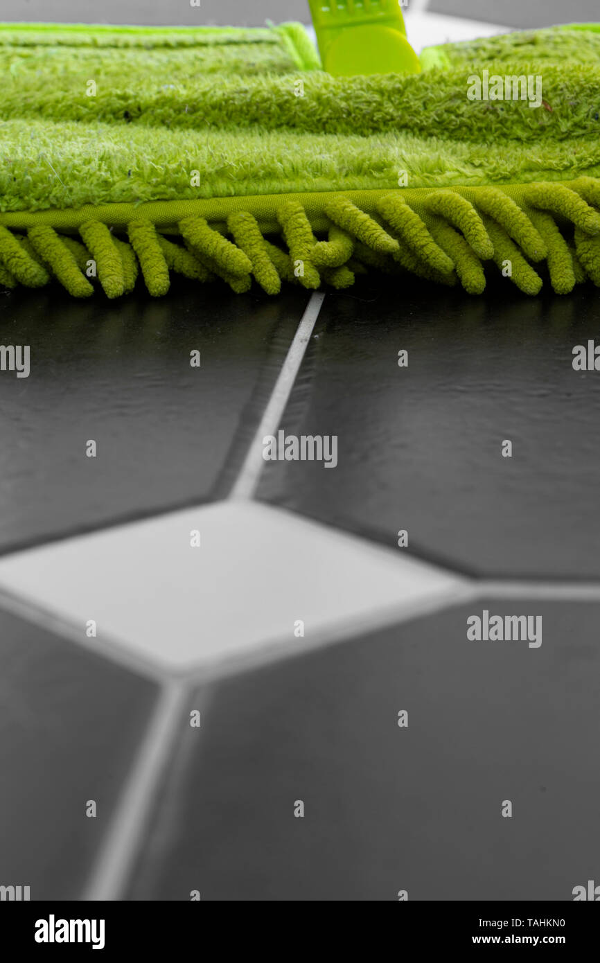 Cleaning tiled floor with a green dry mop head.  Selective colour image. - Stock Image