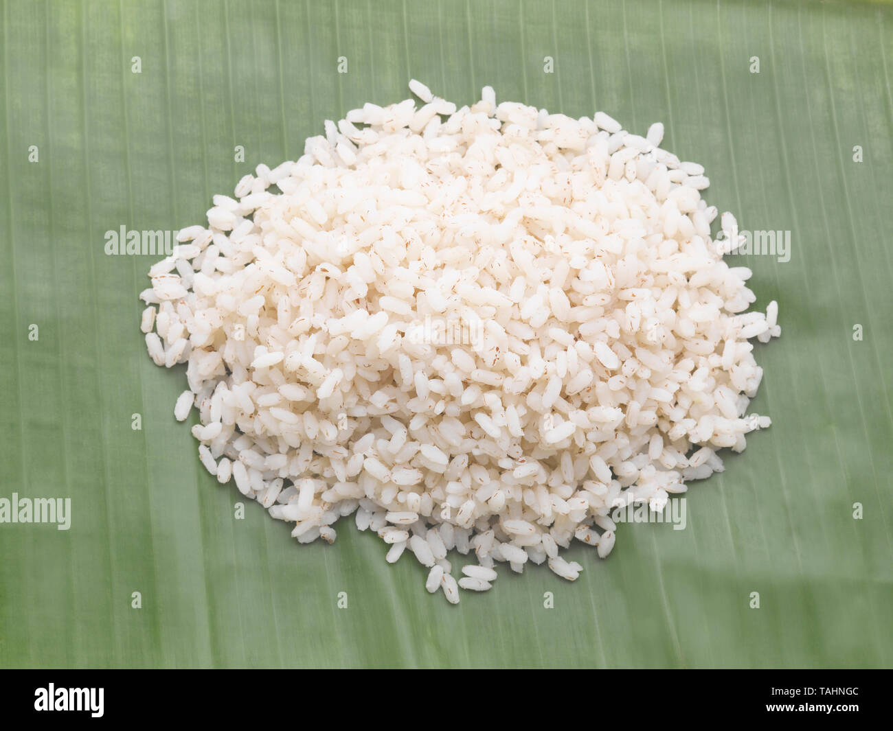 STILL LIFE OF BROWN RICE ON A GREEN PLANTAIN LEAF - Stock Image