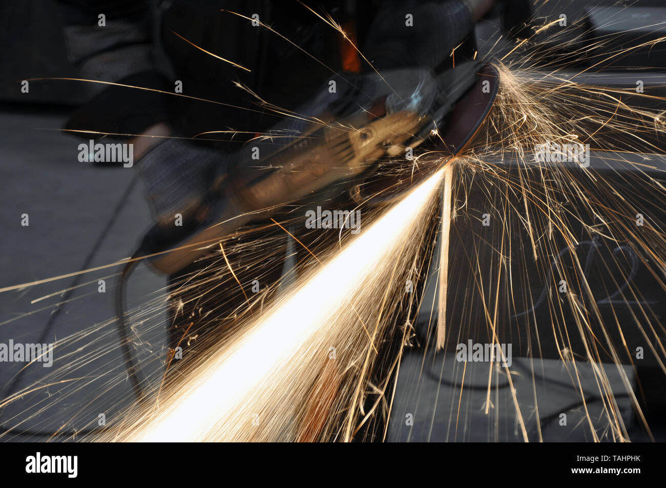 angle grinder. Worker at the factory cuts metal. sparks fly - Stock Image