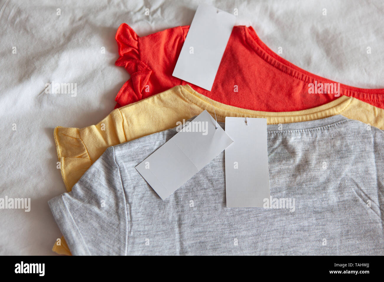 Three new kid's or women's t-shirt, grey, red, yellow colours, with clean label on white background. Concept shopping, summer sales, discounts, organi - Stock Image