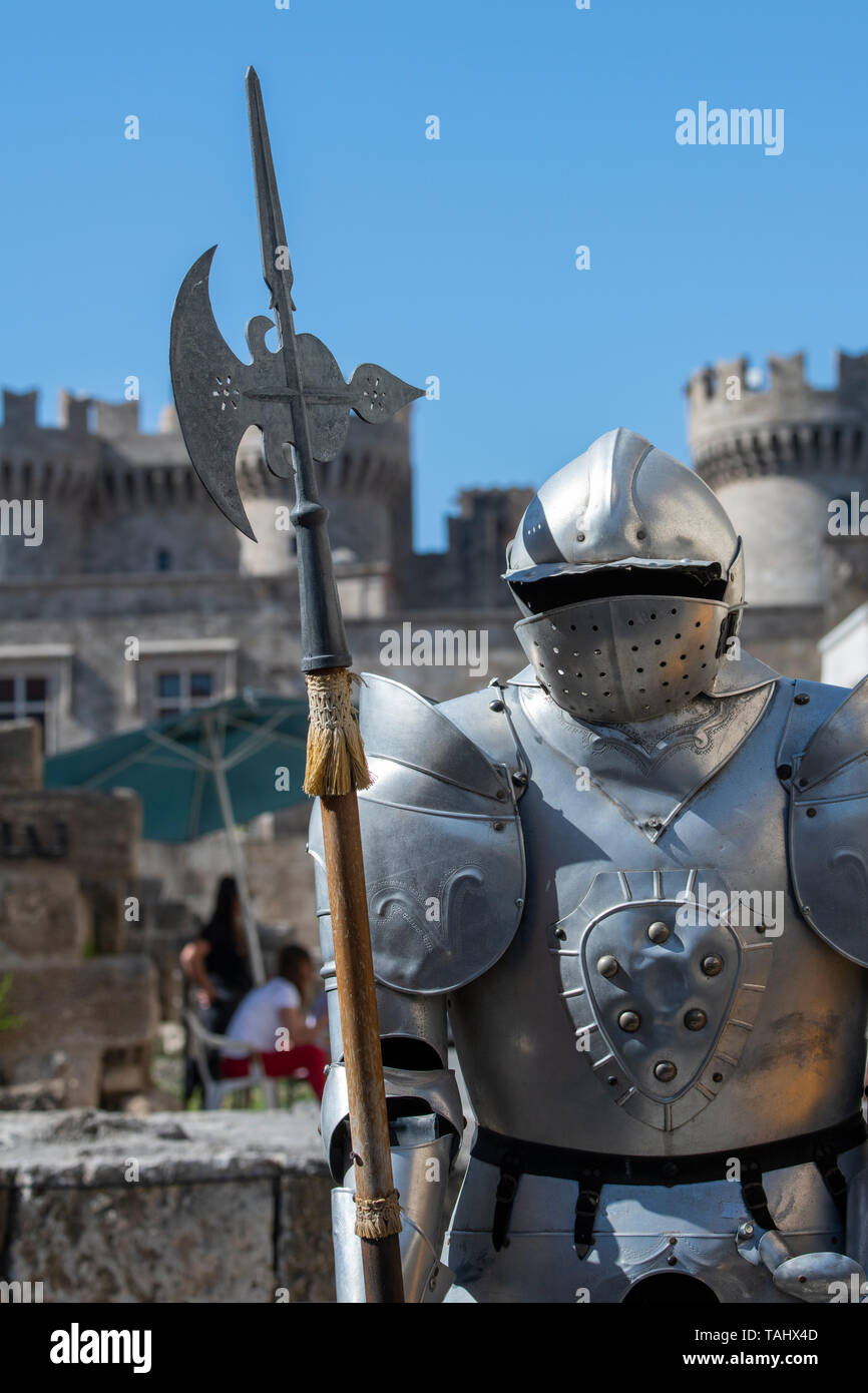 Greece, Rhodes. Medieval Old Town. UNESCO. Suit of armor with Palace of the Grand Master, aka Kastello, in the distance. - Stock Image