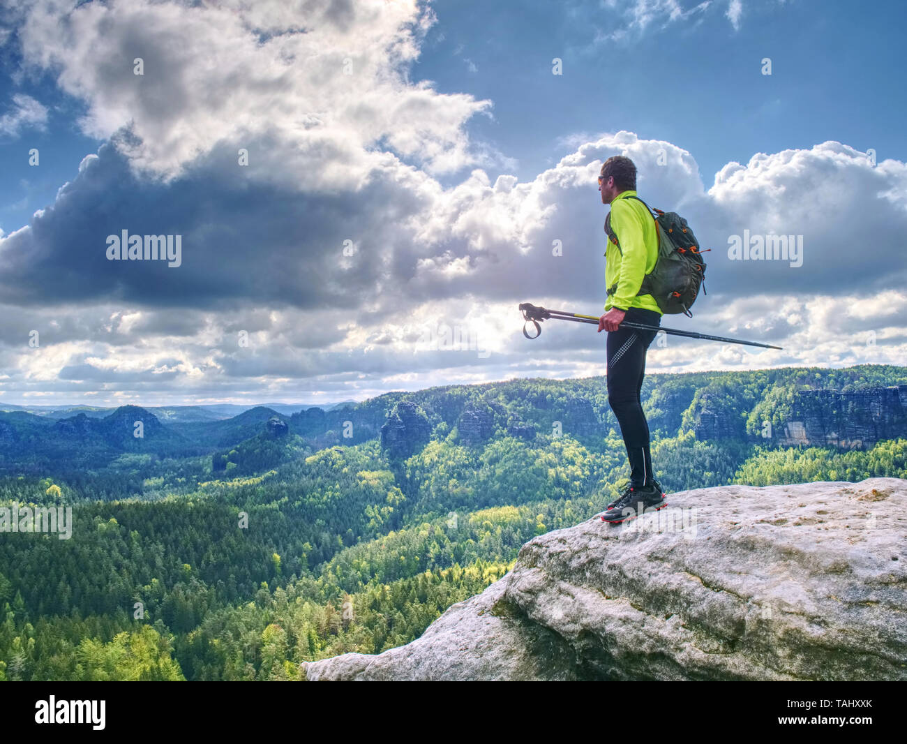 Man trail runner stop on mountain top for relax. Trail athlete in light green lerzey and black leggings on the trail with long deep valley on the back - Stock Image