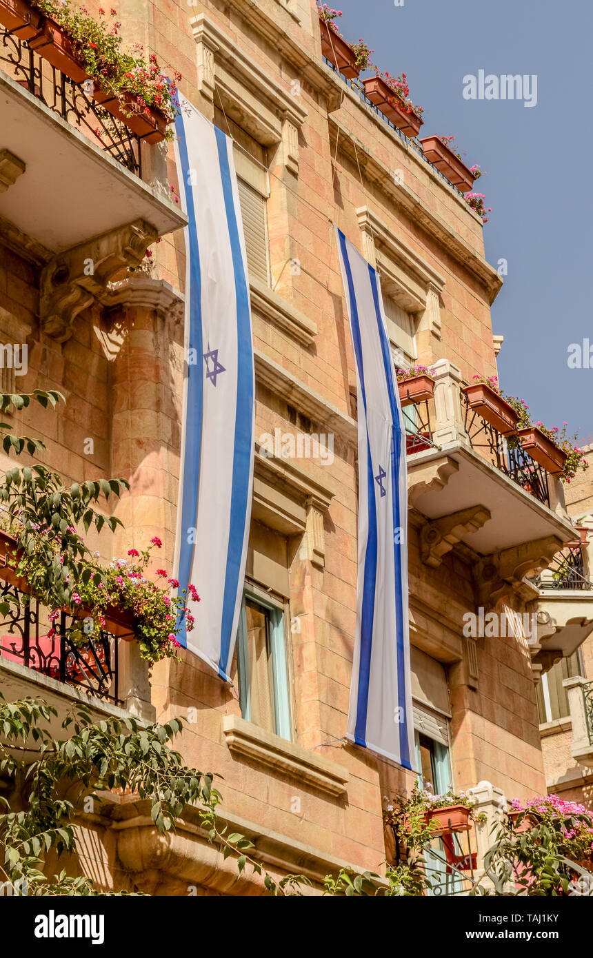 Jewish Star of David flag draping side of building with flowers on balconies on Jaffa Street in Jerusalem, Israel Stock Photo