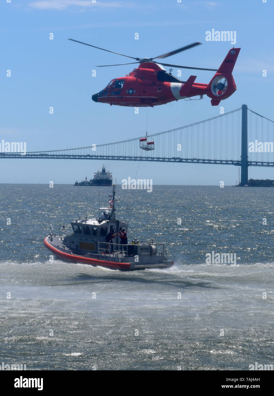 STATEN ISLAND, New York -- May 25, 2019 -- A U.S. Coast Guard HH-65 Dolphin helicopter crew from Atlantic City, New Jersey conducts a Search and Rescue airborne recovery demonstration during Fleet Week New York 2019 at Staten Island's USS The Sullivans Homeport Pier.   Fleet Week New York, now in its 31st year, is the city's time-honored celebration of the sea services. It is an unparalleled opportunity for the citizens of New York and the surrounding tri-state area to meet Sailors, Marines and Coast Guardsmen, as well as witness firsthand the latest capabilities of today's maritime services.  - Stock Image