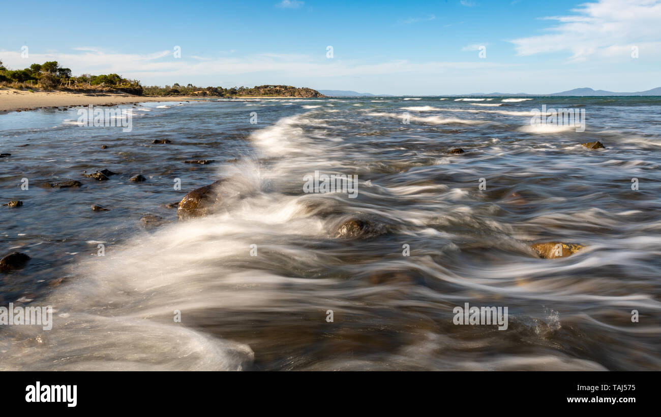 Wave Breaking Over Rocks, Motion Blur, Beach in Background - Stock Image