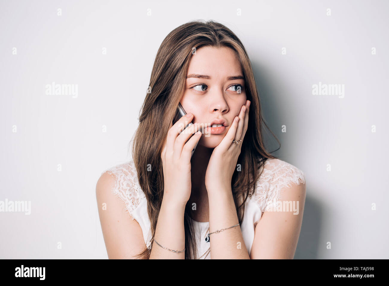 Sad young woman calling the doctor on the phone for a consultation on a white background. Toothache, health concept - Stock Image