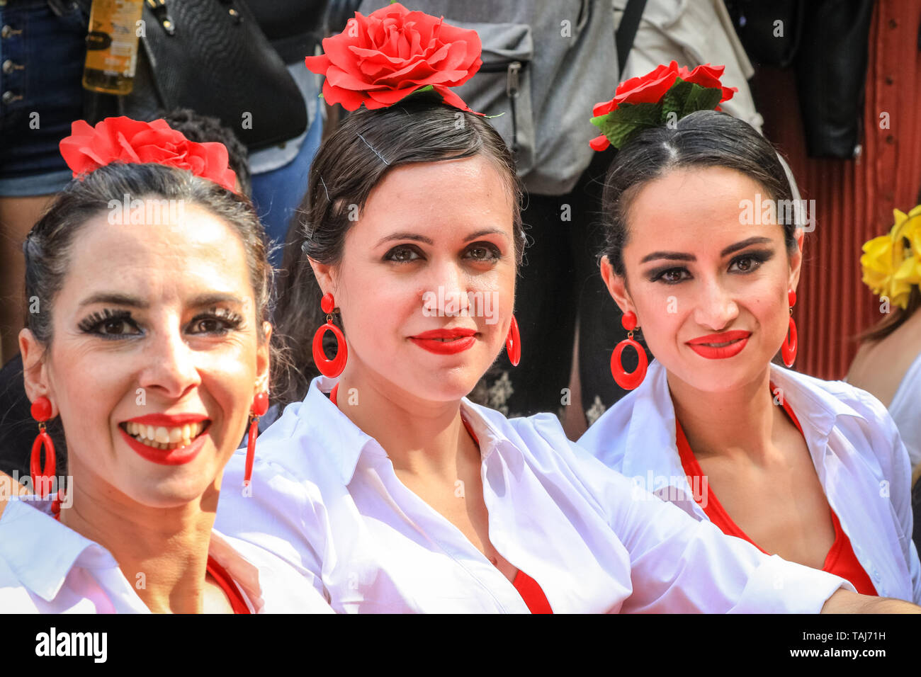 South Bank, London, UK - 25th May 2019. Three beautifully dressed flamenco dancers take a rest on the lawn. The Feria de Londres is a free festival on London's South Bank presenting Spanish culture, dance, music, wine and food from May 24-26. Credit: Imageplotter/Alamy Live News - Stock Image