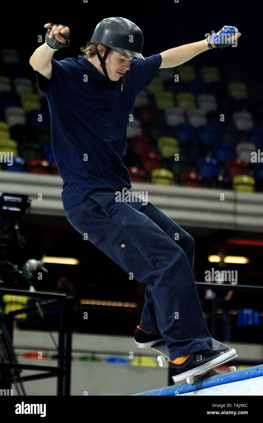 A male skater pulls a trick at the top of the course during