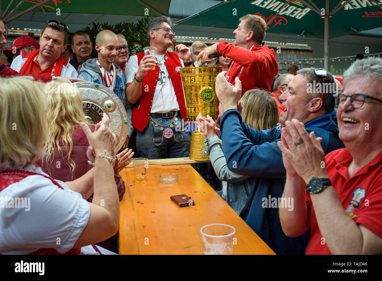 Berlin, Germany. 25th May, 2019. Football, DFB Cup Final RB Leipzig - FC Bayern Munich. The fans of Bayern Munich meet before the game with homemade dummies of the championship cup and the DFB cup in a beer garden on Alexanderplatz. Credit: Gregor Fischer/dpa/Alamy Live News - Stock Image