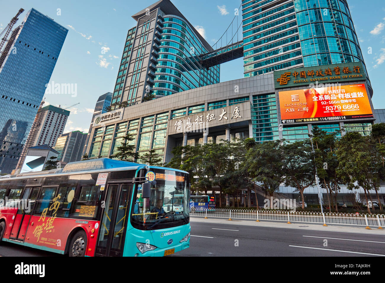 Electric city bus moving on street in Futian Central Business District. Shenzhen, Guangdong Province, China. - Stock Image
