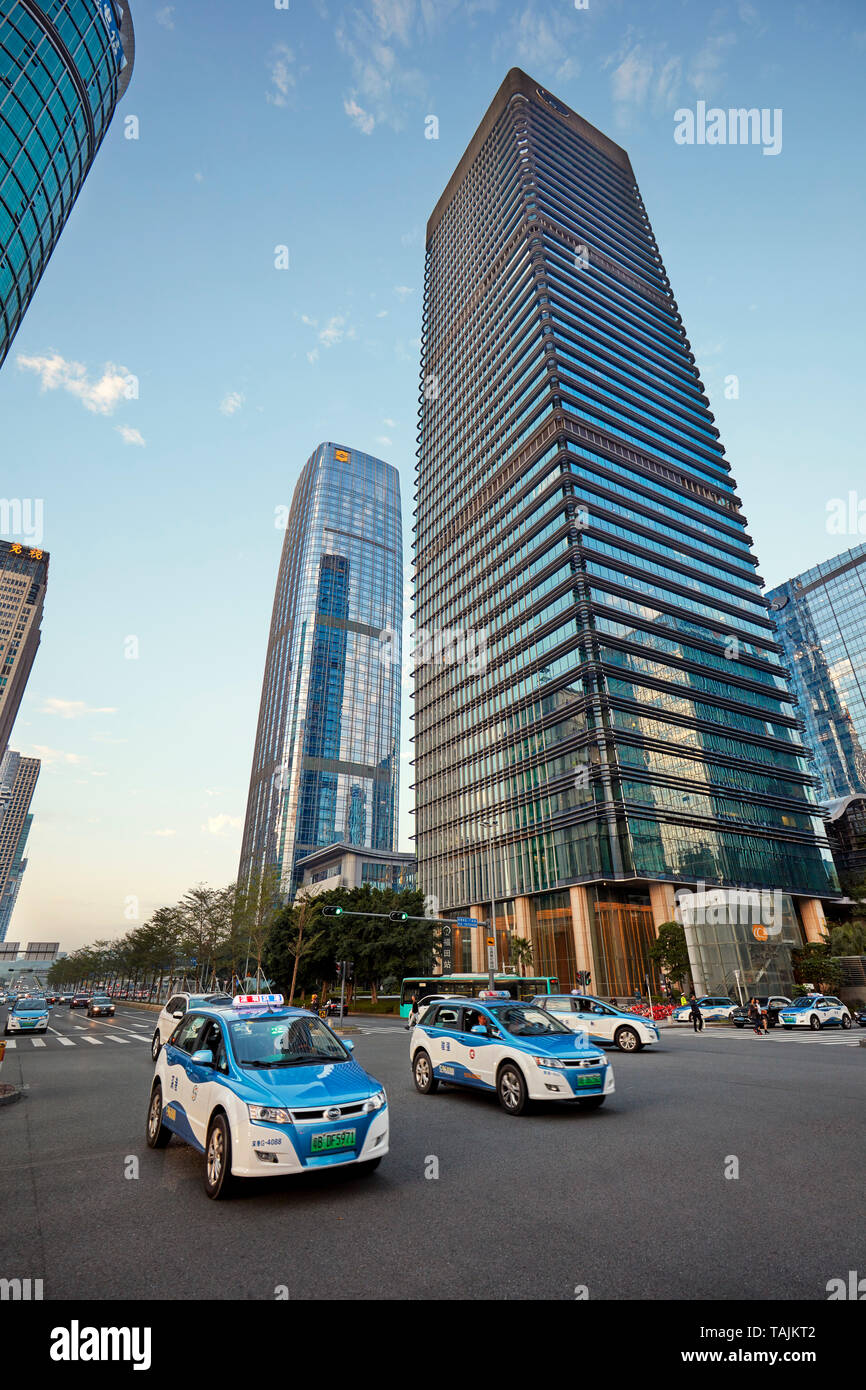 Electric taxi cabs moving on street in Futian Central Business District. Shenzhen, Guangdong Province, China. - Stock Image