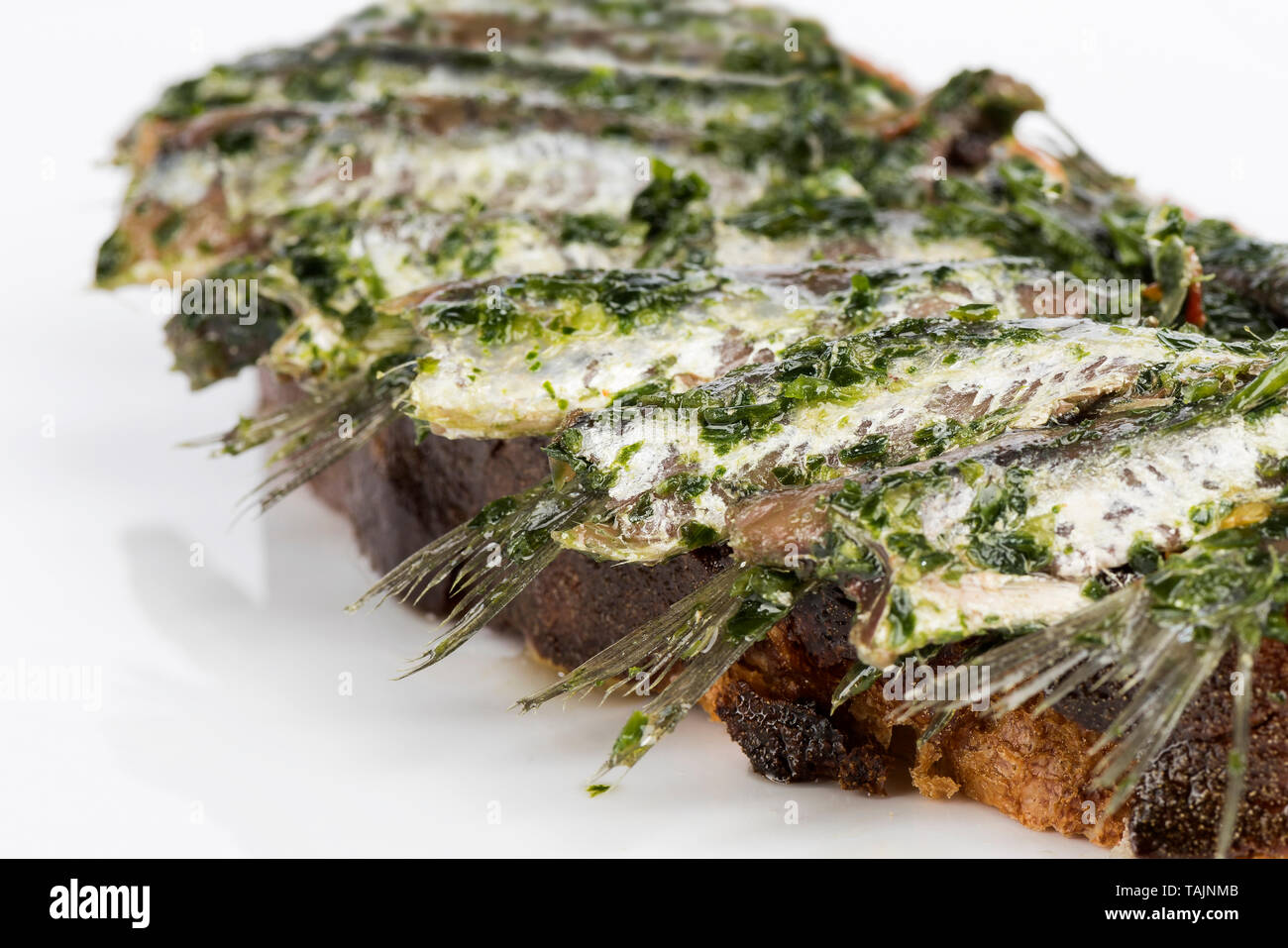 anchovies on bread oil and parsley - Stock Image