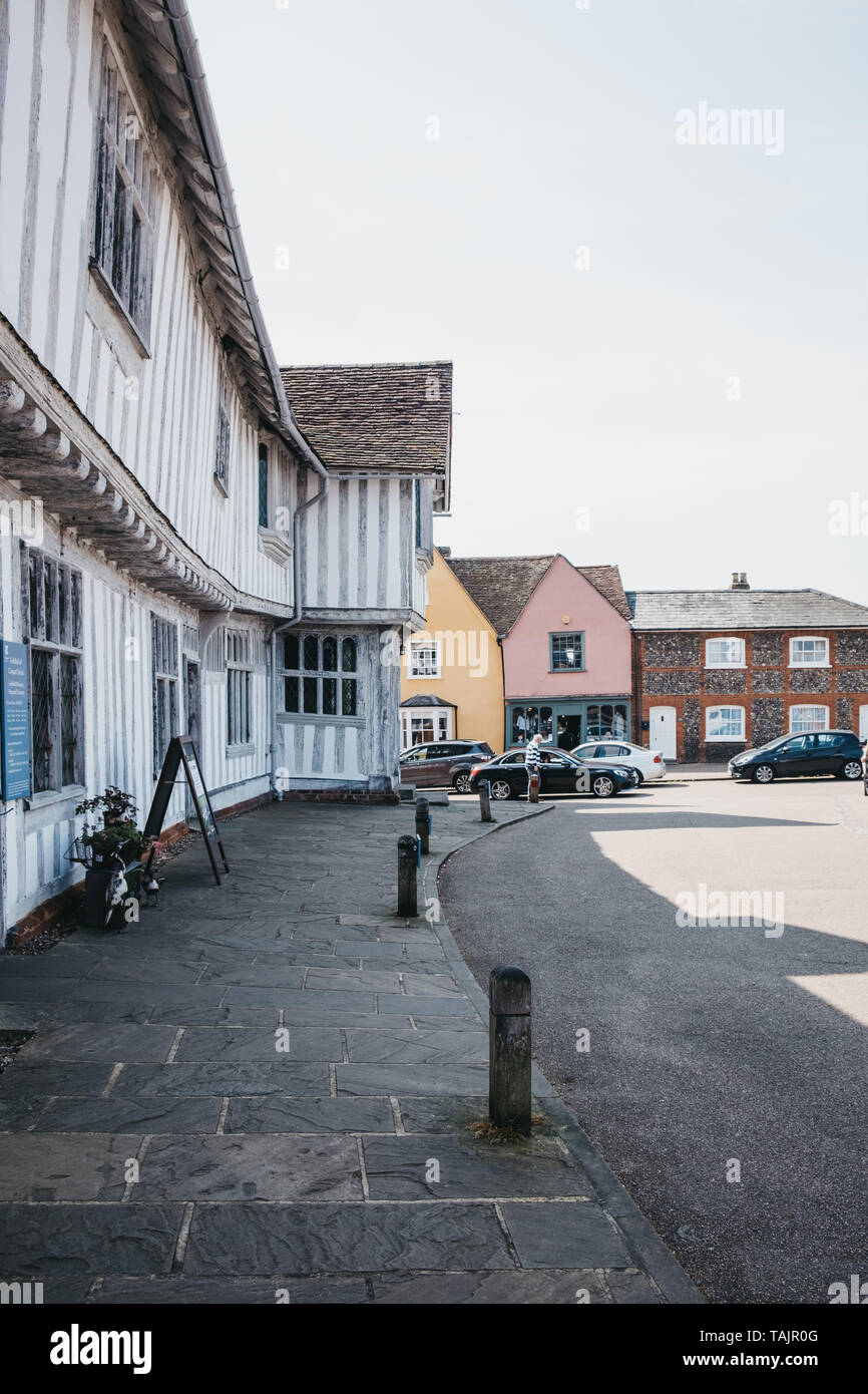 Lavenham, UK - April 19, 2019: Cars driving past half-timbered medieval cottages in Lavenham, a village in Suffolk, England, famous for its Guildhall, - Stock Image