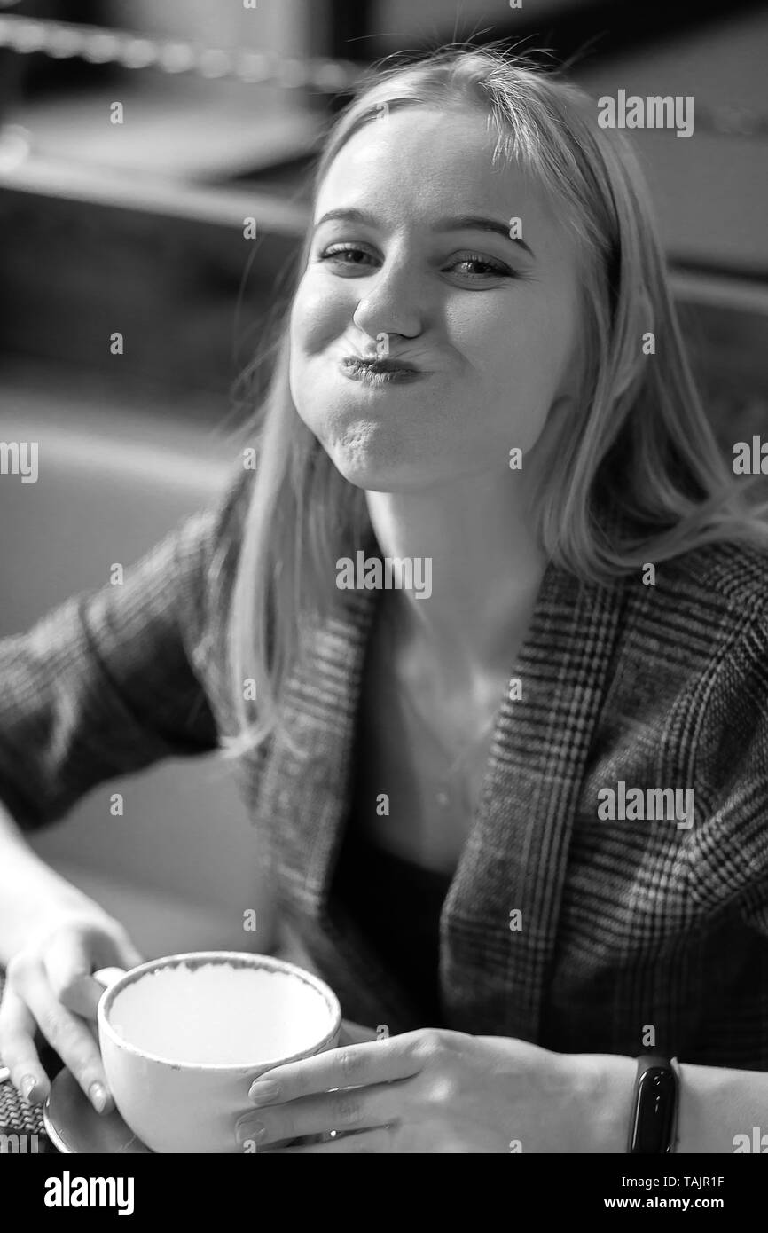 fun young blond woman with cup of tea in cafe looking at camera smiling, grimacing monochrome - Stock Image