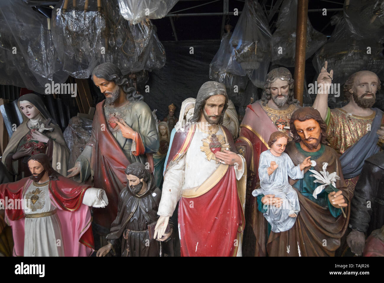 Discarded Roman Catholic Christian statuettes stored in a shed - Stock Image