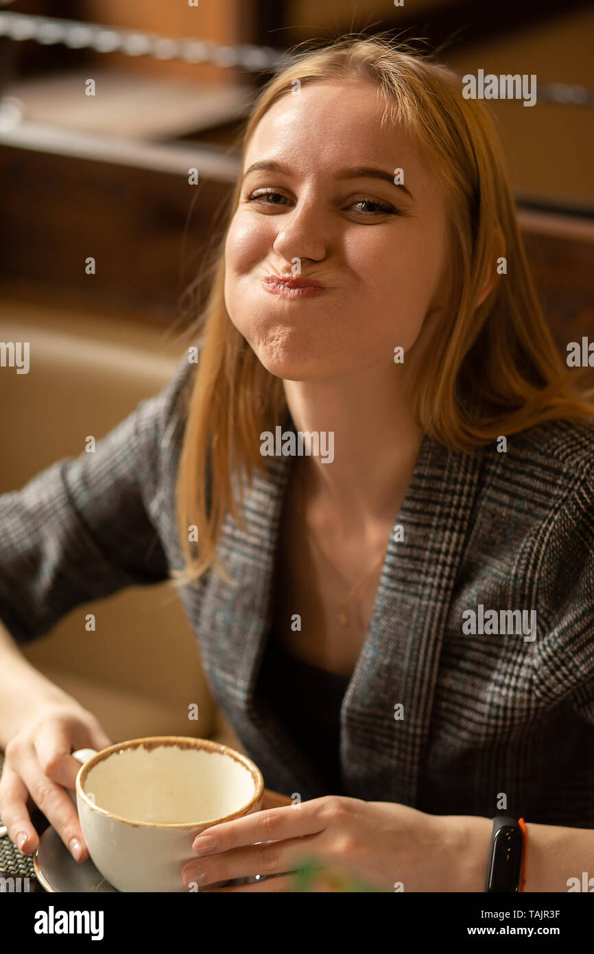 fun young blond woman with cup of tea in cafe looking at camera smiling, grimacing - Stock Image
