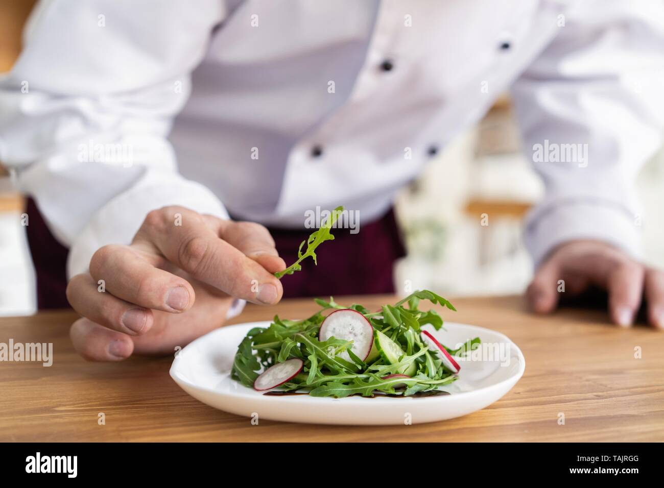 Male Cook Chef Decorating Garnishing Prepared Salad Dish On The Plate In Restaurant Commercial Kitchen Stock Photo Alamy