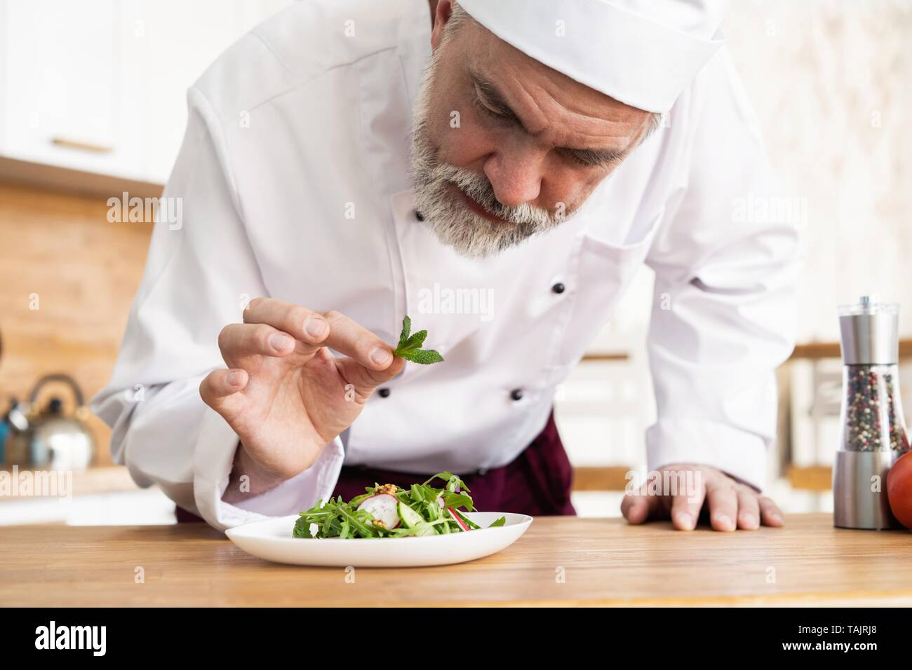 male cook chef decorating garnishing prepared salad dish on ...