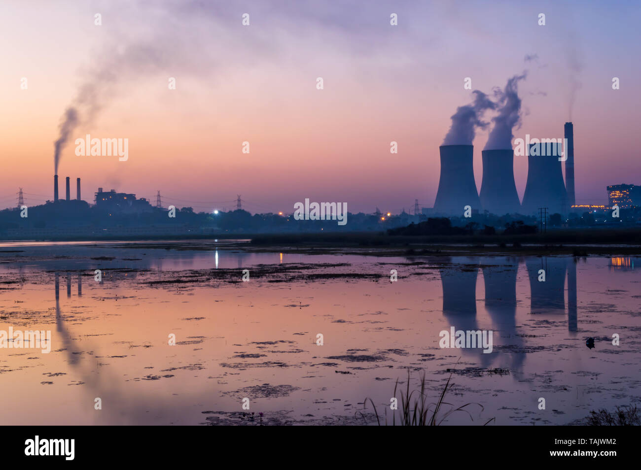 Coal powered thermal power plant emitting smoke and steam from chimney and cooling tower. Reflection of cooling tower and chimney on lake. Stock Photo