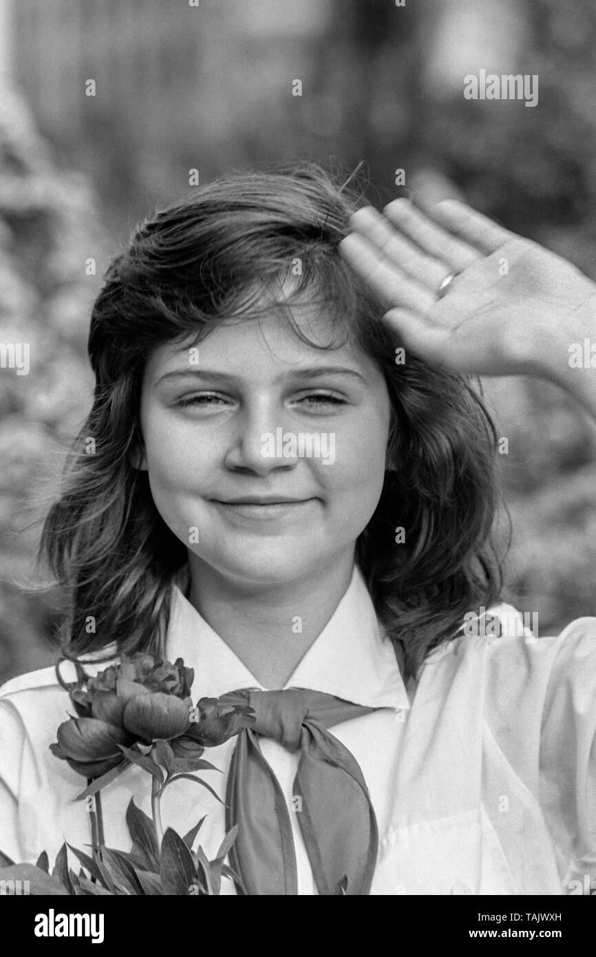 young schoolgirl member of the pioneer movement wearing her necktie and uniform while holding a bunch of flowers and saluting 1970s hungary Stock Photo