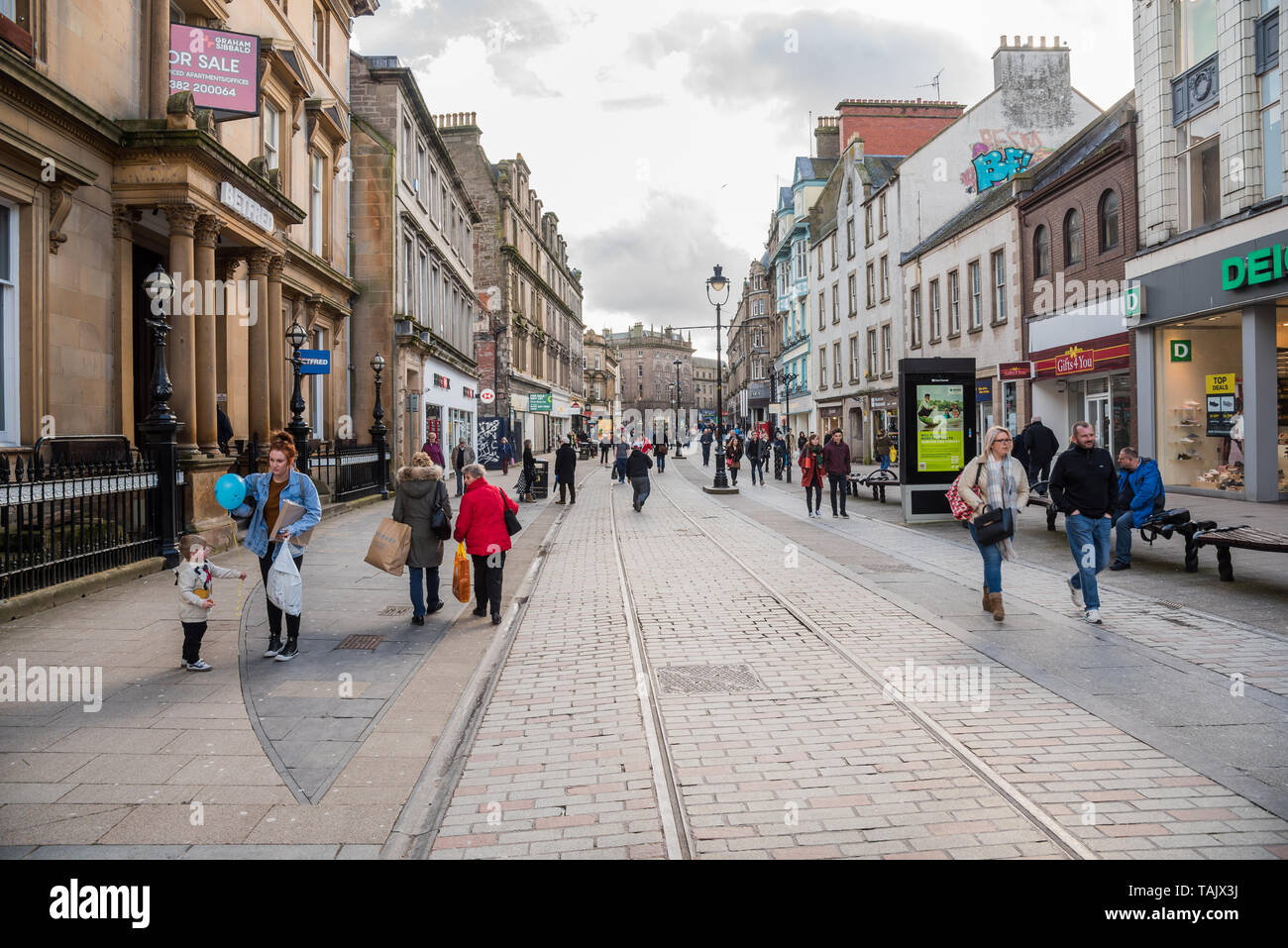 Dundee, UK - March 8, 2018: people strolling along a shopping pedestrian streeton a cloudy winter day - Stock Image